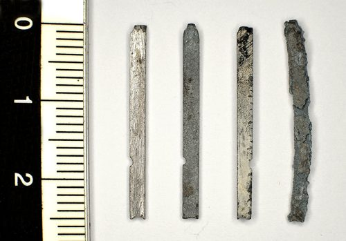 Figure 1. Four types from left to right: without corrosion; with an even dark grey corrosion; with a dense white layer of passive corrosion and finally an example of a vigorously corroded item that has lost all structural rigidity, form and readability.